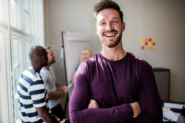 Laughing young designer standing in an office after a presentation - Stock Photo - Images