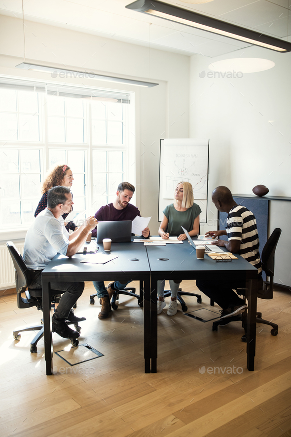 Group of diverse designers talking together around an office table - Stock Photo - Images