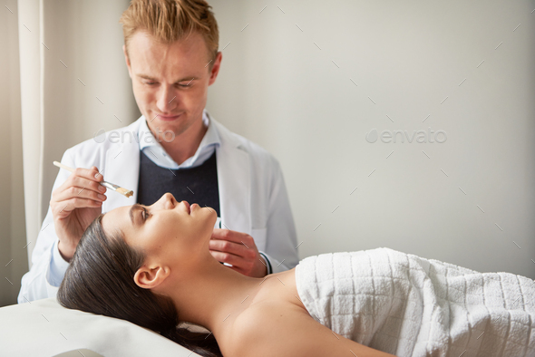 Male cosmetologist making facial mask for woman - Stock Photo - Images