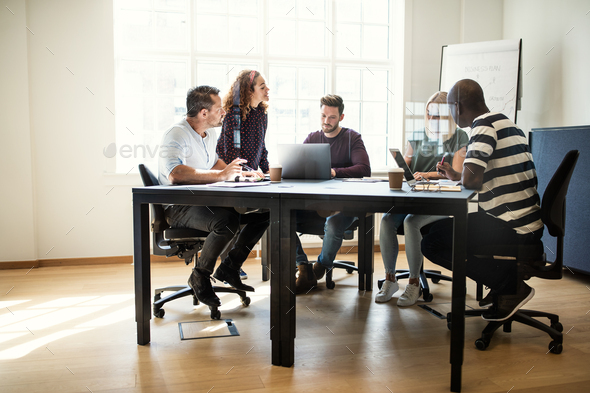 Designers having a meeting together around an office table - Stock Photo - Images