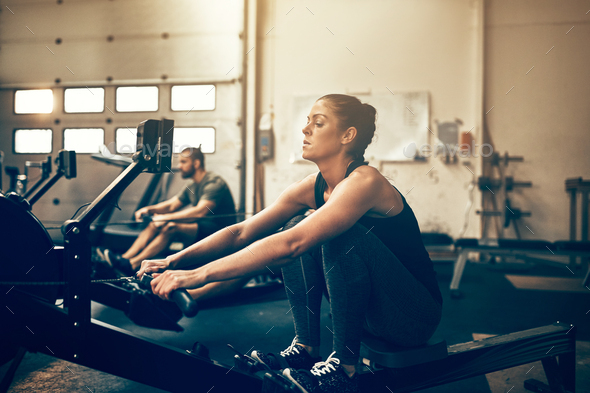 Two fit people exercising on rowing machines at the gym - Stock Photo - Images