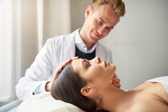 Woman lying in salon while beautician looking on face - Stock Photo - Images