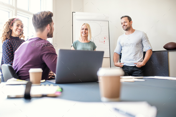 Smiling group of designers talking together after a boardroom presentation - Stock Photo - Images