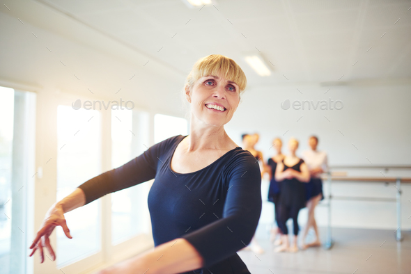 Smiling mature woman practicing ballet in a dance studio - Stock Photo - Images