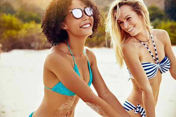 Smiling women wearing bikinis standing on a sandy beach - Stock Photo - Images