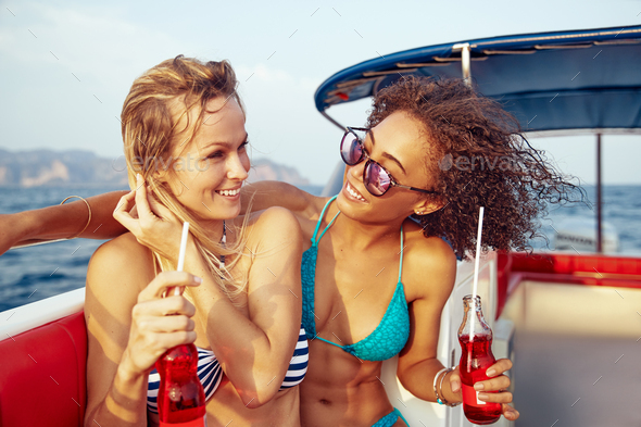 Laughing female friends having fun on a boat during vacation - Stock Photo - Images