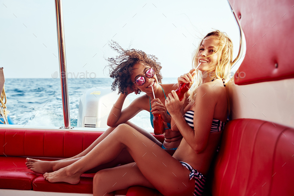 Smiling young friends in bikinis having drinks on a boat - Stock Photo - Images