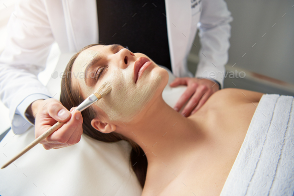 Unrecognizable cosmetologist applying mask on female face at cosmetology procedure - Stock Photo - Images
