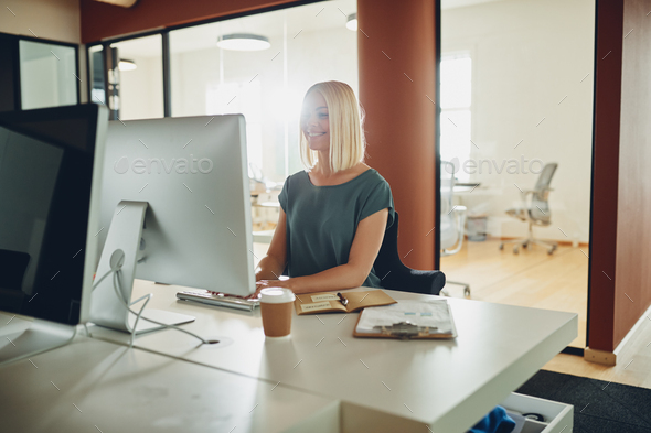 Young businesswoman smiling while working online at her office desk - Stock Photo - Images