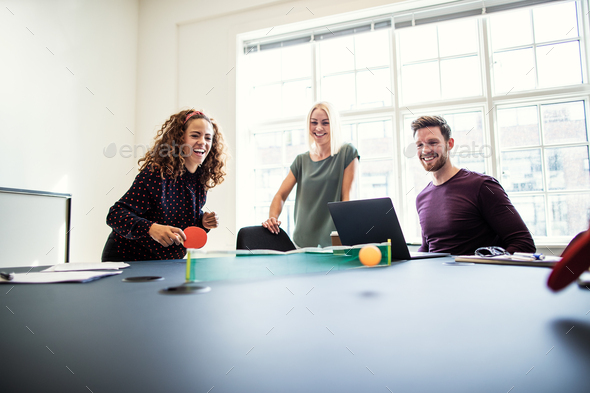 Laughing office colleagues playing table tennis during a work break - Stock Photo - Images