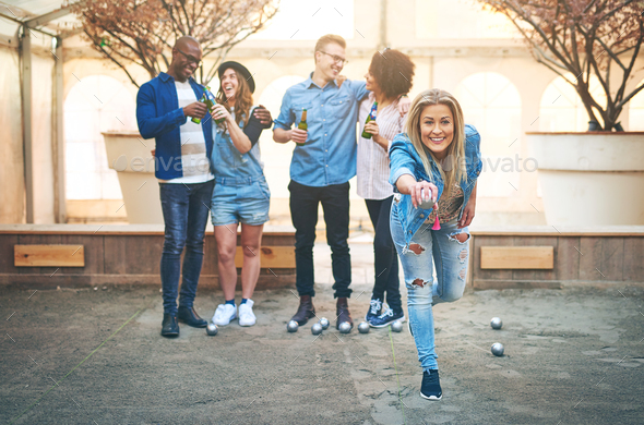 Drinking beer multiethnic friends playing petanque on court - Stock Photo - Images