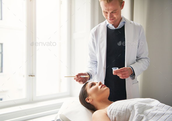 Smiling male cosmetologist moisturizing female face with mask - Stock Photo - Images