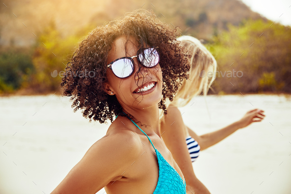 Smiling young woman walking with a friend at the beach - Stock Photo - Images