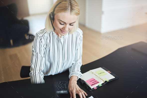 Businesswoman talking with her client on a headset at work - Stock Photo - Images