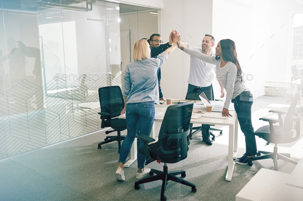 Smiling colleagues standing together around an office table high fiving - Stock Photo - Images