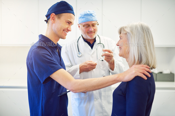 Young doctor cheering adult female patient in clinic - Stock Photo - Images