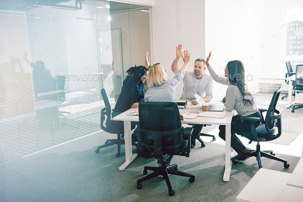 Smiling coworkers sitting around an office table high fiving together - Stock Photo - Images