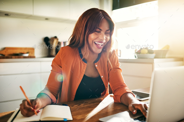 Laughing young female entrepreneur working online in her kitchen - Stock Photo - Images