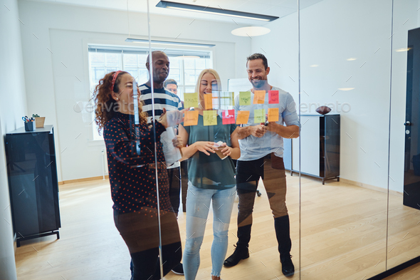 Designers smiling during an office brainstorming session - Stock Photo - Images