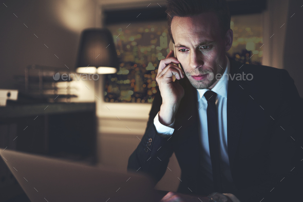 Intelligent businessman talking smartphone and surfing laptop - Stock Photo - Images