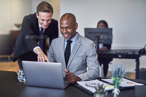 Two businessmen looking at something on a laptop at work - Stock Photo - Images