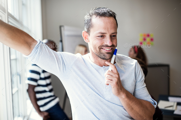Designer smiling after a whiteboard presentation to office colleagues - Stock Photo - Images
