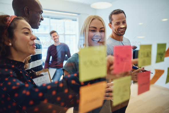 Smiling designers brainstorming together on an office wall - Stock Photo - Images