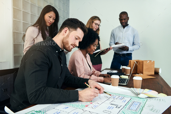 Male architect working on blueprints with colleagues in an office - Stock Photo - Images