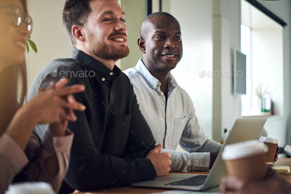 Diverse businesspeople smiling while sitting together in a boardroom - Stock Photo - Images