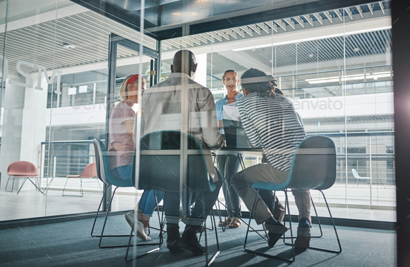 Young businesswoman meeting with her team in a boardroom - Stock Photo - Images