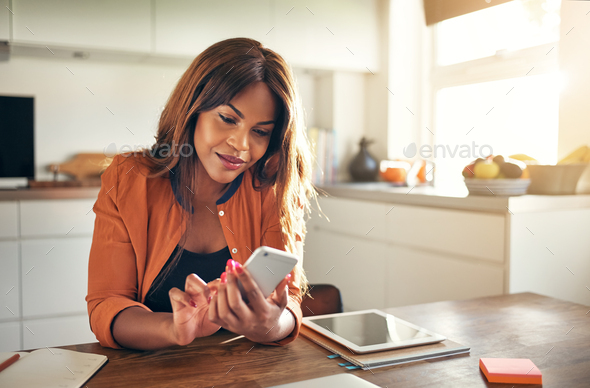 Young entrepreneur reading texts while working at her kitchen table - Stock Photo - Images