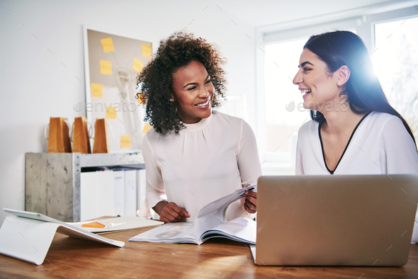 Two happy businesswomen laughing together - Stock Photo - Images