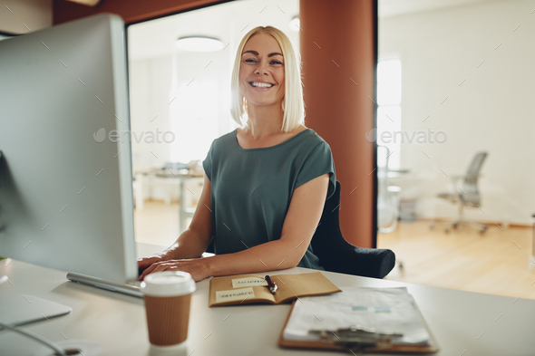 Young businesswoman smiling while working at her office desk - Stock Photo - Images