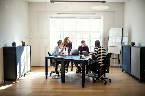 Diverse group of designers meeting together around an office table - Stock Photo - Images