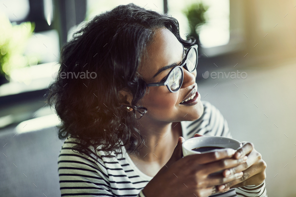 Young African woman smiling and drinking coffee in a cafe - Stock Photo - Images