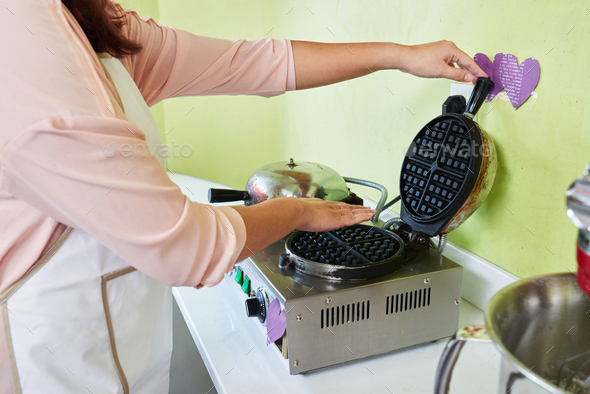 Checking waffle maker - Stock Photo - Images