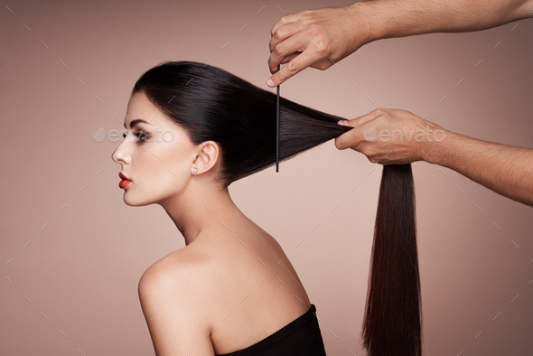 Hairdresser combs the hair of a woman - Stock Photo - Images
