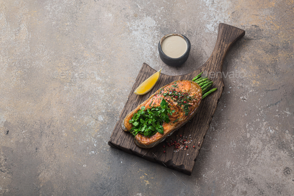 Fried salmon steak with asparagus on wooden board, copy space - Stock Photo - Images