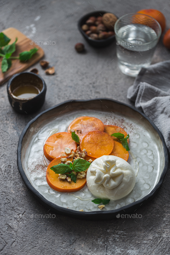 Persimmon and buratta cheese with nuts and honey - Stock Photo - Images