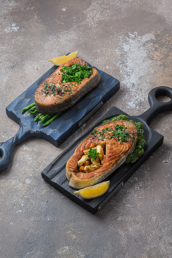 Two salmon steaks with vegetables on wooden boards, copy space - Stock Photo - Images