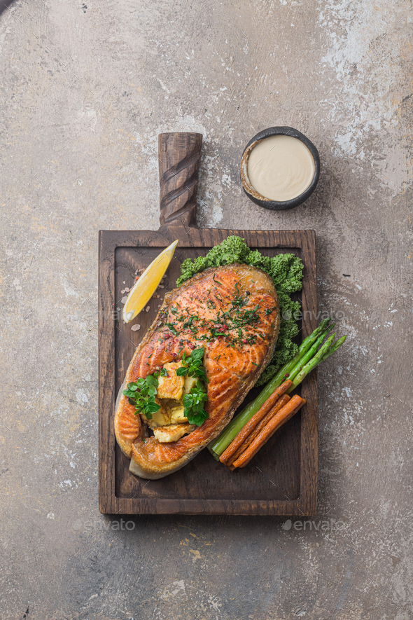 Fried salmon steak with vegetables on wooden board, copy space - Stock Photo - Images