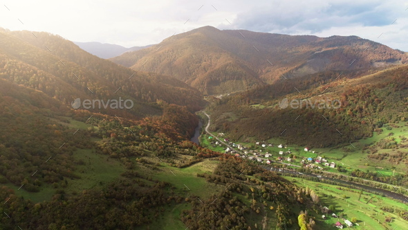 mountain village buildings at river against brown hillpeaks - Stock Photo - Images