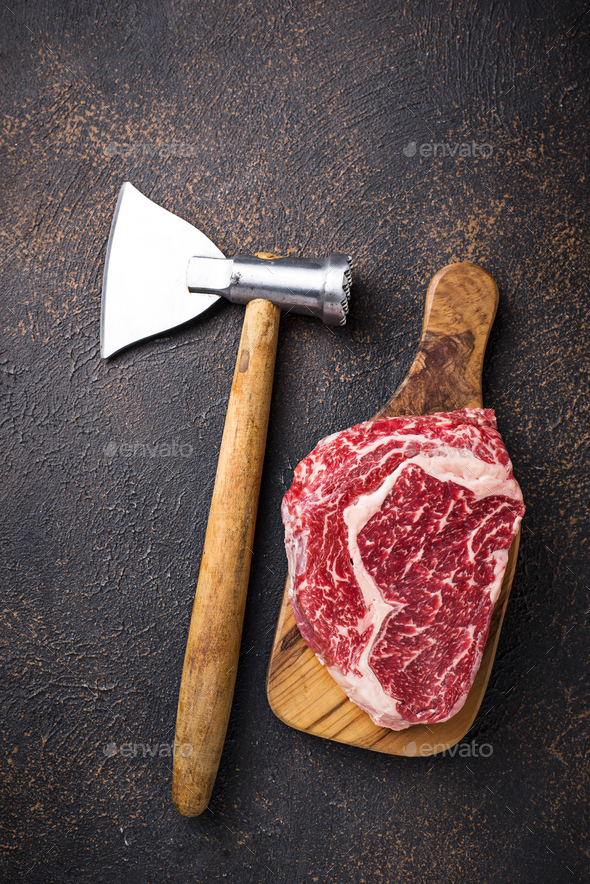 Raw marbled ribeye steak and butchers knife - Stock Photo - Images
