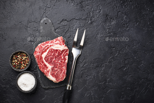 Raw marbled ribeye steak and spices - Stock Photo - Images