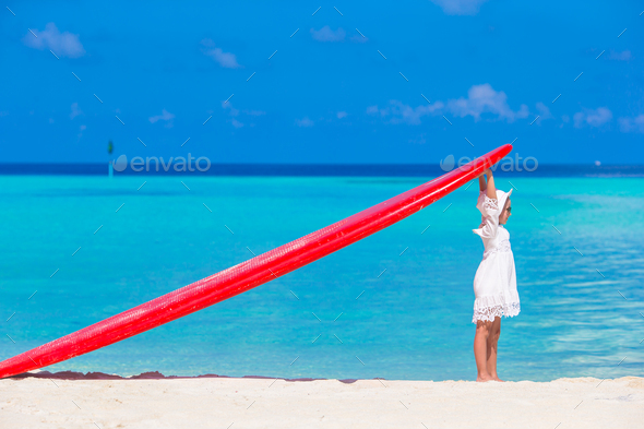 Adorable little girl with red big surfboard on tropical white beach - Stock Photo - Images
