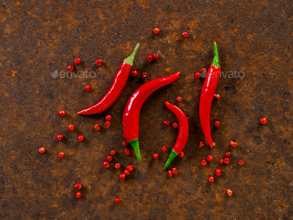 Red hot chili pepper pods and peas on dark metallic rusty background, top view - Stock Photo - Images