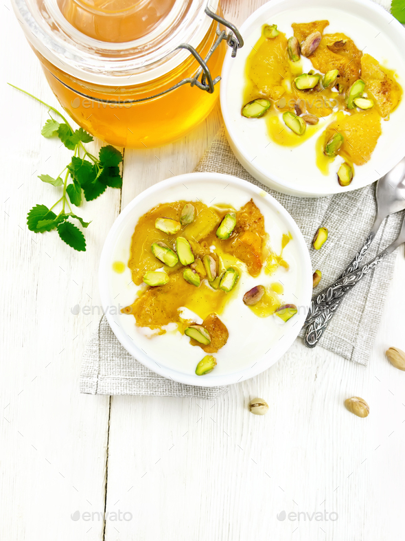 Dessert of yogurt and persimmon two bowls on light board top - Stock Photo - Images