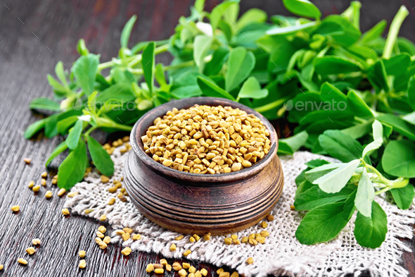 Fenugreek in bowl with leaves on board - Stock Photo - Images