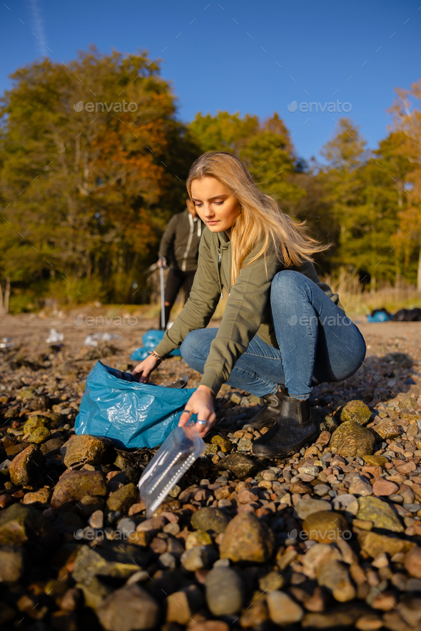 Young woman picking up plastic at rocky beach - Stock Photo - Images
