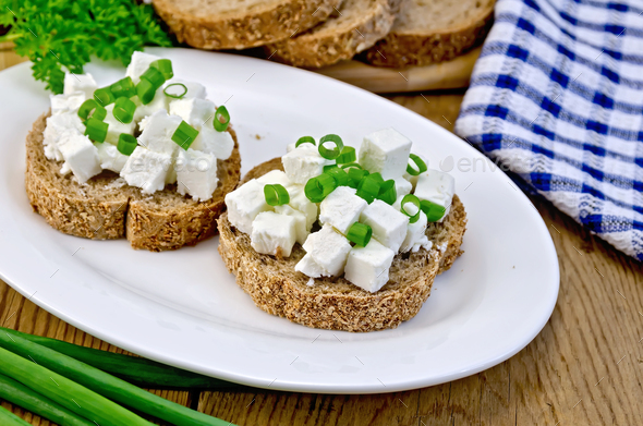 Bread with feta cheese and green onions on a board - Stock Photo - Images